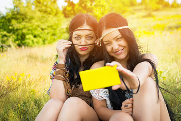 Two boho fashion sisters taking a selfie on smartphone