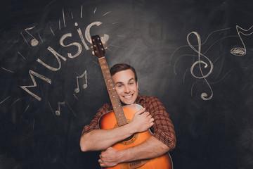 Happy young smiling musician huging his guitar