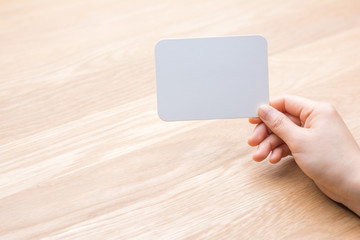 woman's hand holding white blank paper