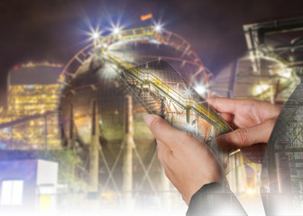 Double exposure of woman hand hold and touch screen smart phone, tablet,cellphone and Energy oil refinery Factory at night as Energy and Technology concept.