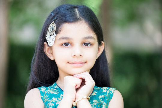 Closeup portrait, young girl resting placing face on hands, isolated outside outdoors background