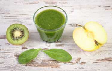 Cocktail from spinach, kiwi and apple on old wooden background, healthy nutrition