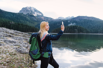 View of young woman standing near lake while carrying backpack and taking picture by using smartphone