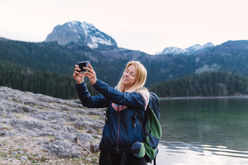 Young female hiker taking photo of herself near the mountain lake