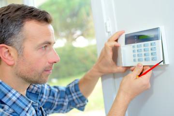Obraz Electrician fitting an intrusion alarm - fototapety do salonu