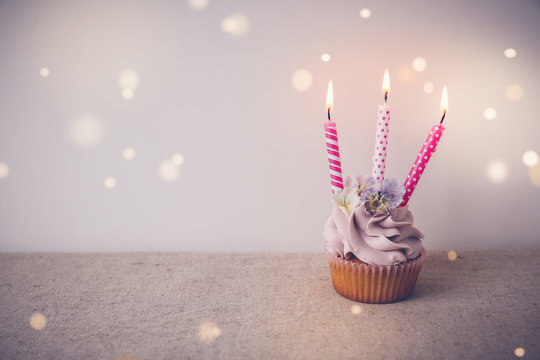 Pink and purple Birthday cupcake with three candles, fairy light toning background