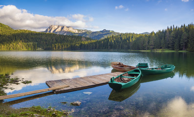Wall Mural - Durmitor National Park, Montenegro,sunrise over a mountain lake, the peaks of the mountains lit by the rising sun