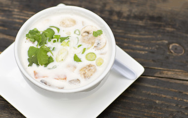 Thai soup in a white dish on a wooden table. Spicy coconut milk soup with shrimp and greens.