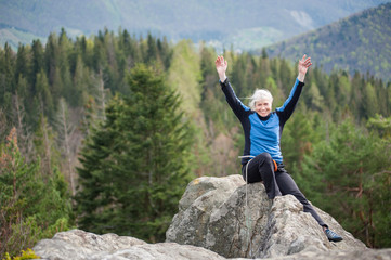 Happy woman in a blue jacket with hands up and with climbing equipment sitting on the top of the rock on the blurred background of forest valley.