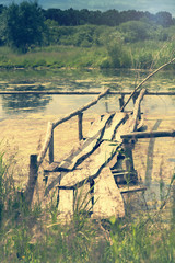 Old wooden bridge over the lake overgrown with grass. Coloring and processing photos in vintage style with soft selective focus. Shallow depth of field