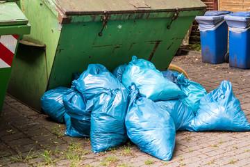 Gestapelte blaue Müllsäcke am Container