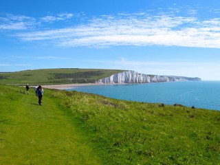 Hikers approach white cliffs of the Seven Sisters in Eastbourne, East Sussex, England
