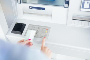 Girl using ATM machine.
