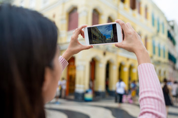 Woman taking photo by cellphone in Macau