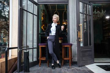 Stylish fashion blogger posing at cafe