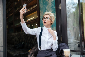 Stylish young woman taking selfie in cafe