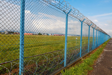 Barbed wire fence of a restricted area under blue sky