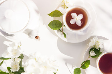 Top view on cup of tea with jasmine flower and vase of jasmine flowers on the garden table.