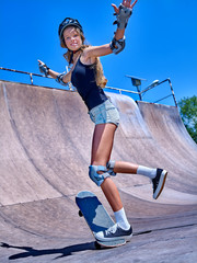 Teen girl wearing skateboard helmet rides his skateboard outdoor.
