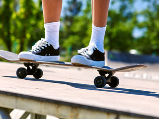 Legs skateboard close up in skatepark. Low section of child legs skate on skateboard.