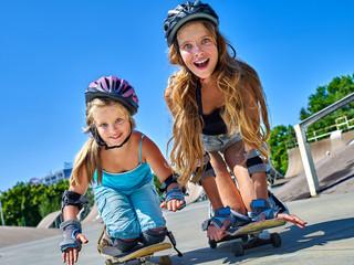 Two girl children in skateboard helmet skateboard on his skateboard outdoor. Low section.