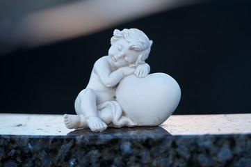 Grabschmuck. Weißer Engel hält ein Herz am Friedhof.