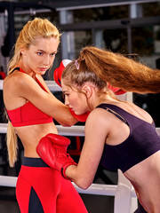 Two boxing women wearing red boxing gloves are boxing on boxing ring.