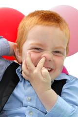 Frecher rothaariger Junge popelt in der Nase