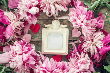 Background with pink peony and frame with an angel on the old bo