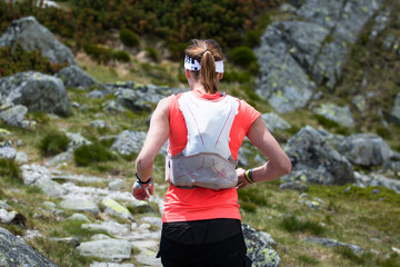 ultra trail runner woman with backpack training running in high mountains terrain