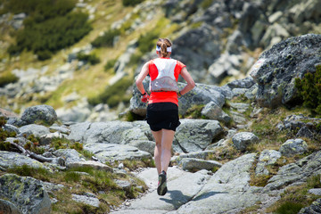 young woman training running on the trail in high mountain alpine nature