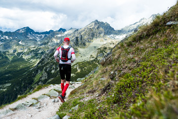 middle age man in sportswear running on trail in  high mountain scenery with peaks