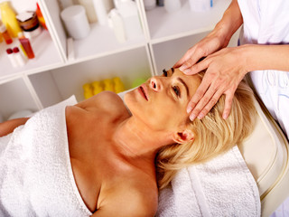 Woman middle-aged take face and neck massage in massage salon.