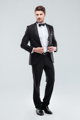 Full length of handsome young man in tuxedo with bowtie