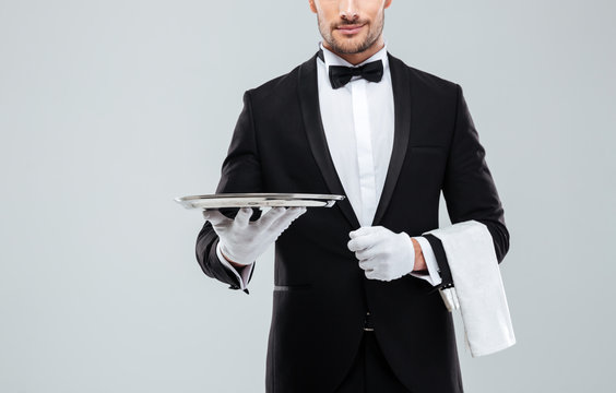 Waiter in tuxedo holding metal empty tray and napkin