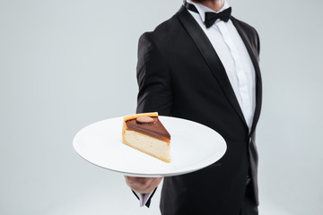 Waiter in tuxedo holding plate with piece of cake