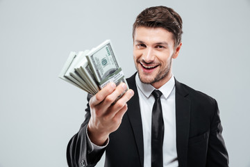 Closeup of cheerful young businessman holding money