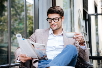 Handsome young man with magazine drinking coffee in outdoor cafe