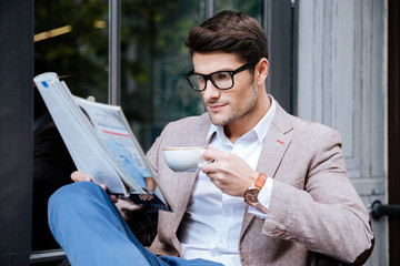 Concentrated man with coffee and magazine sitting in outdoor cafe