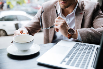 Cropped image of businessman holding cup and using laptop indoors