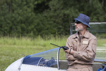 A man in sunglasses and in a hat leaning on glider with a radio in his hand