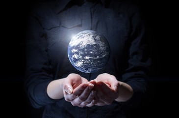 Businesswoman holding Earth planet in palm. Elements of this ima