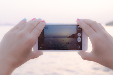 View Landscape Sunset on a woman's with colorful nails mobile smart phone