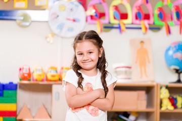 Preschooler girl posing in classroom.