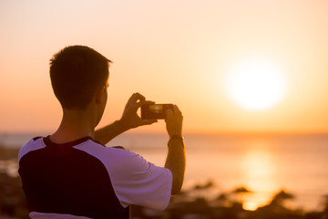 Young man taking photo of sea sunset