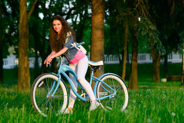 Joyful young woman on a bicycle in the green park at sunset