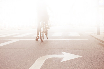 Fototapete - Woman on bike into the bright