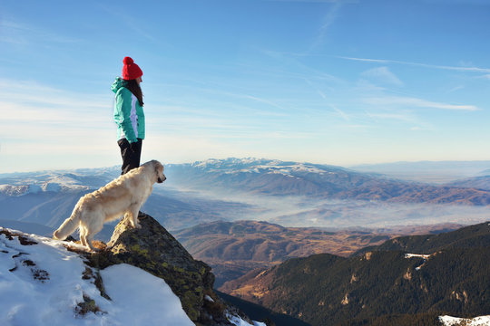 Girl with a golden retriever dog on top of a mountain during winter watching a beautiful landscape