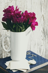 Pink flowers of a peony. Bouquet of pink peonies in a white jug, an old photo album, old empty photographs and a pocket watch against the white painted board