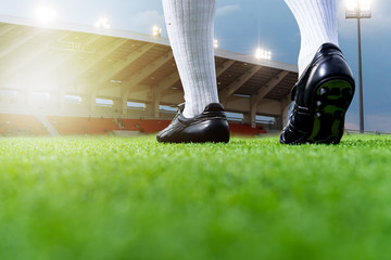 Foot of soccer player or football player walk on green grass ready to play soccer match for the winner with soccer stadium backgrounds.